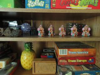 shelf with games, figurines, art, cards, plastic pineapple bank, carved box