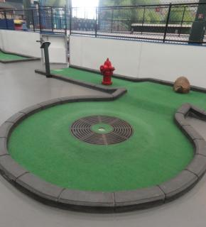 indoor miniature golf hole with fire hydrant and manhole cover