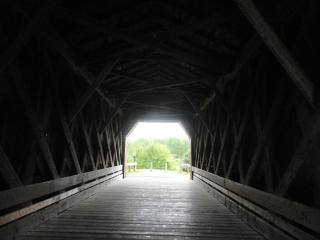 covered bridge, from dark interior, view of tree in sunlight at the end