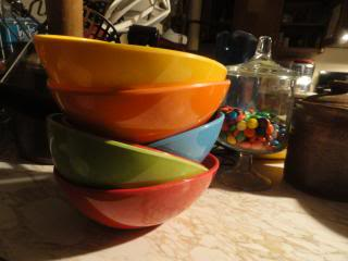 stack of colorful bowls, next to glass container of colorful M&Ms