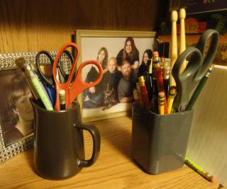 pens and scissors in cups, with framed photos behind