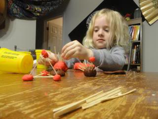 child making pyramids with toothpicks and playdough