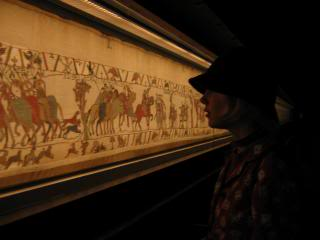 Holly's profile against the museum-lit Bayeux Tapestry