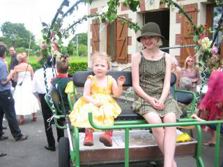 Holly and Sophie riding in a decorated cart at a French wedding