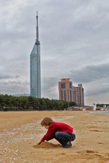 child on a beach with a glass skyscraper behind