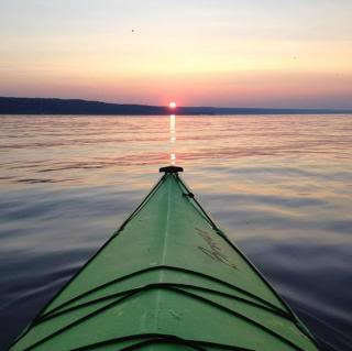 front of a kayak, pointing at the setting sun