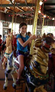 child on carousel horse
