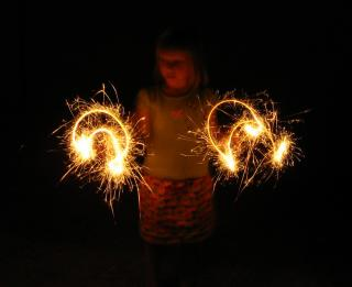 child with two sparklers in the dark