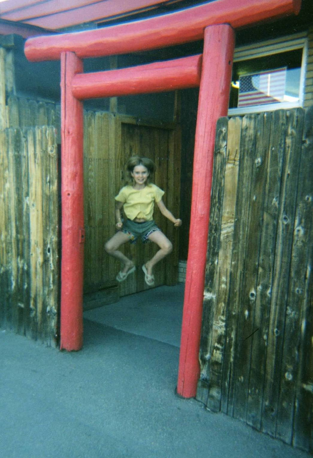 child Holly - leaping off the ground framed by the torii of the dojo - American flag in the window